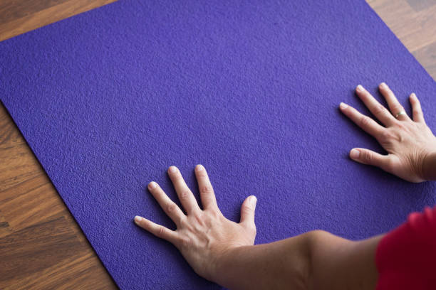 Close up on hands of woman on purple yoga mat while performing downward facing dog stock photo