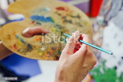 937313030 istock photo Close up on hands of young woman female painter art holding a painting brush and artist palette with colors painting 1190056046