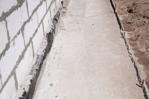 Close-up op huis Stichting waterdicht maken, vochtige proofing met contrete pad naar water lekken voor thuis muur te voorkomen. foto