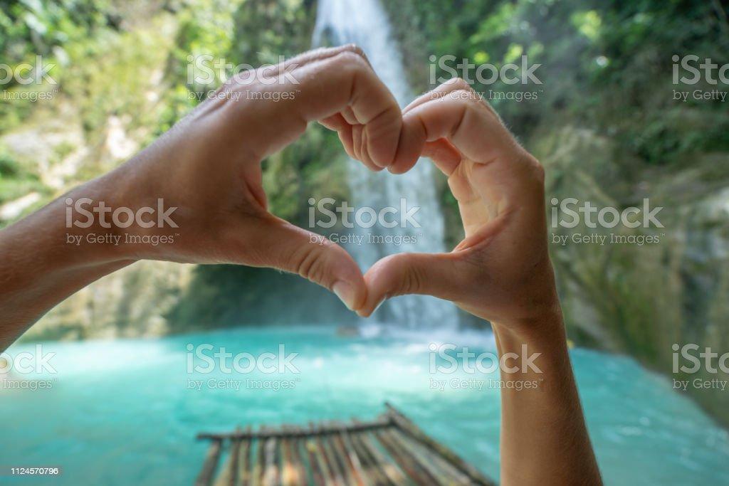Young woman loving beautiful waterfall making a heart shape finger...