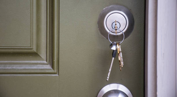 Close up on Keys inside Front Door of New Home ownership at new suburb real estate stock photo