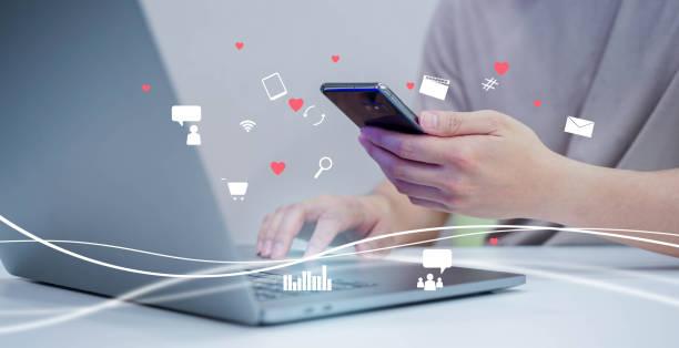 インターネットネットワーク技術とビジネスコンセプトのためのソーシャルメディアマーケティングの未来的な作業にラップトップ上のデータを検索してダウンロードしながら、アプリケー� - 広告 ストックフォトと画像