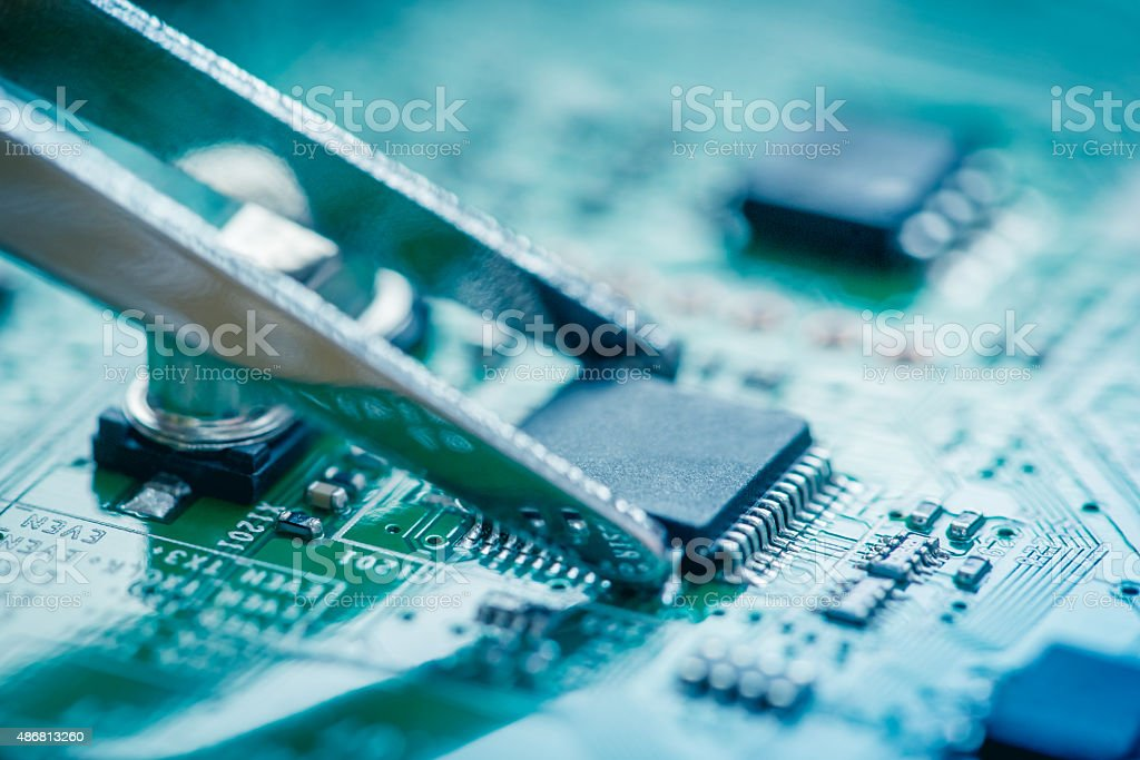 Close up on microchip catching with tweezers on circuit board. stock photo