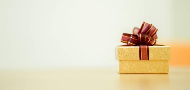 nahaufnahme auf mini goldenen geschenk-box mit rotem band auf schreibtisch für besonderen tag wie weihnachten, geburtstag, frohes neues konzept - originelle geburtstagsgeschenke stock-fotos und bilder