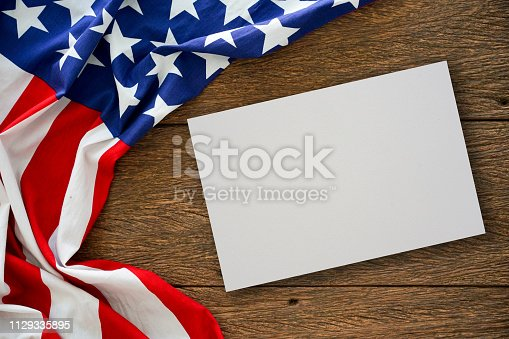 579407234 istock photo close up on mock up white paper texture with vintage crumpled retro of America flag on wood table top background for design concept 1129335895