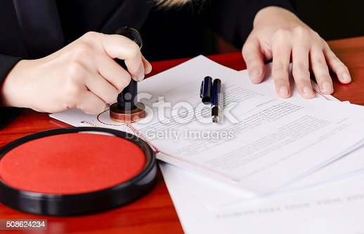 854317150istockphoto Close up on notaries  public hand stamping the testament 508624234