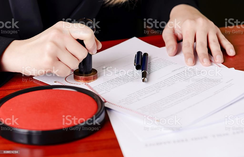 Close up on notaries  public hand stamping the testament stock photo