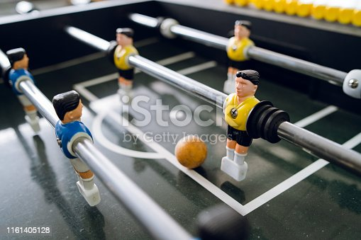 Close up on players of Table football soccer kicker foosball top-table game playing
