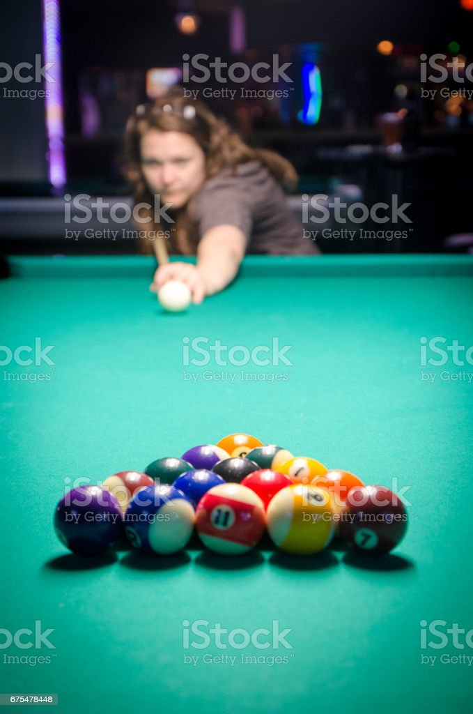 Close up on rack of pool cue balls on the green table while player is...