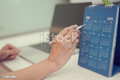 1073023470istockphoto close up on senior businesswoman hand using pen writing or mark on date calendar for note or make appointment at office desk , senior working concept 1128013994
