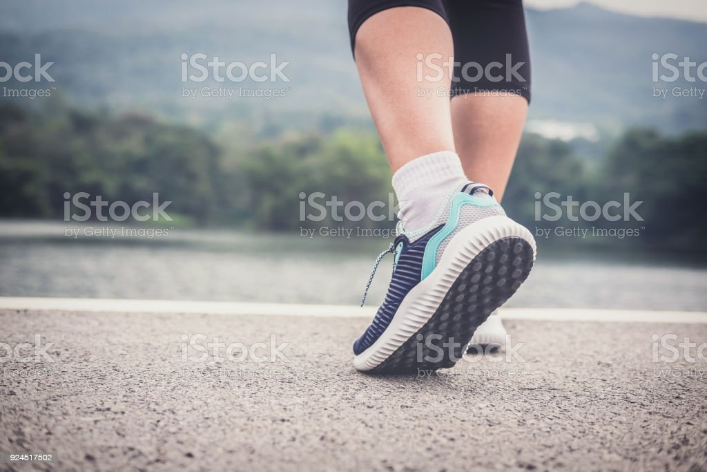 Close up on shoes, woman walking on running track stock photo