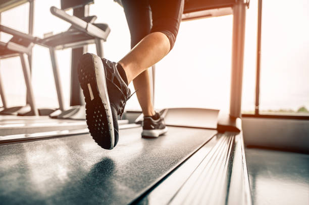 Close up on shoe,Women running in a gym on a treadmill.exercising concept.fitness and healthy lifestyle Close up on shoe,Women running in a gym on a treadmill.exercising concept.fitness and healthy lifestyle treadmill stock pictures, royalty-free photos & images