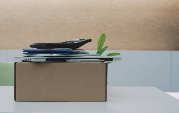 close up on tan box carton with group of object such as laptop ,tablet, calculator and calendar lay on the top at office table after cleaning and prepare for move , work concept - oggetti personali foto e immagini stock