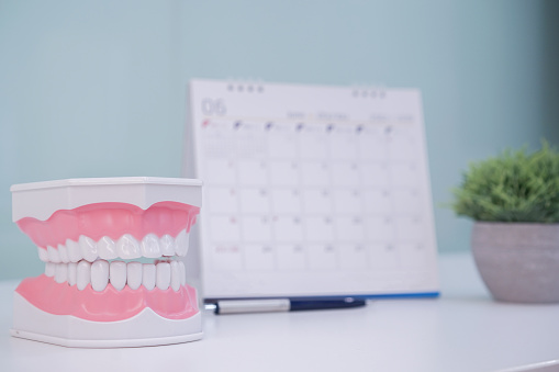 istock close up on teeth model denture with standing calendar for make appointment at dentist's office table , healthcare concept 1144750329