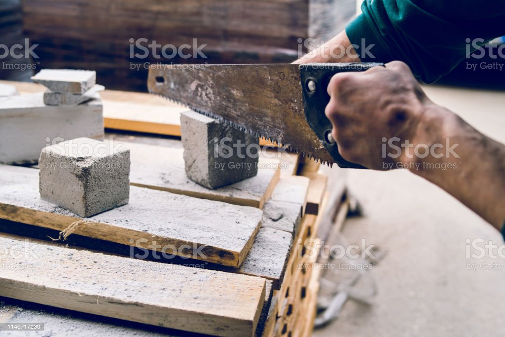 Close up on the construction worker using the hand saw to manually...