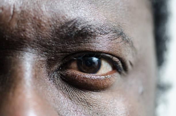 Das linke Auge von einem schwarzen jungen Erwachsenen Mann hautnah – Foto