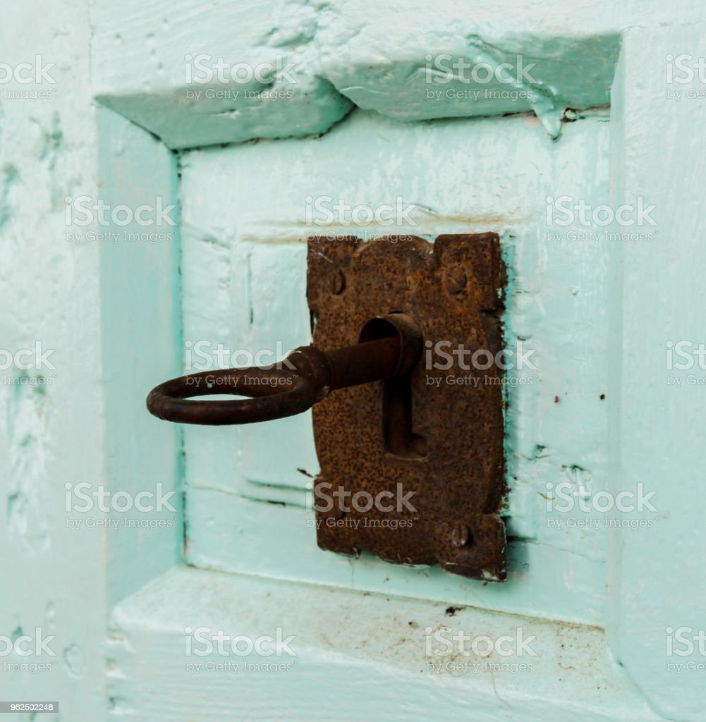 close up on the old lock and key with an interesting texture on the door - Royalty-free Aging Process Stock Photo