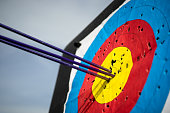 Close up on three arrows in the middle center of the target goal achieved success archery