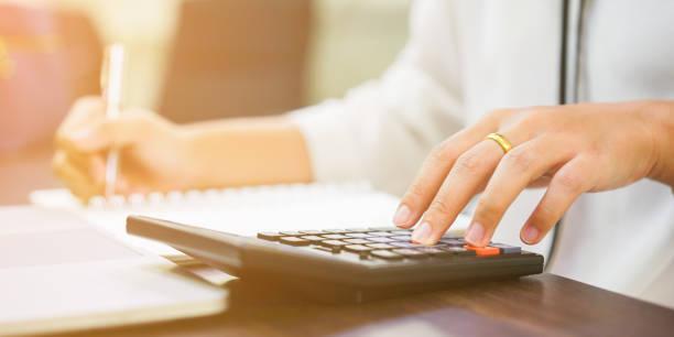 cerrar en mano de mujer pulsando en calculadora para calcular estimar el costo, mayor concepto de trabajo de trabajo contable - gerente de cuentas fotografías e imágenes de stock