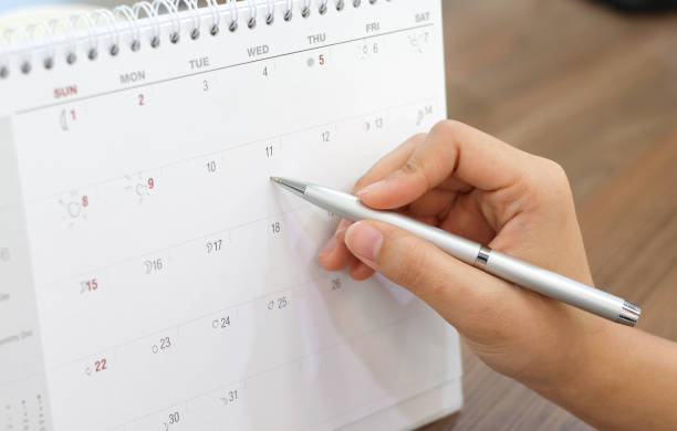 close up on woman hand with pen writing on calender for note or make appointment concept. close up on woman hand with pen writing on calender for note or make appointment concept. making a reservation stock pictures, royalty-free photos & images