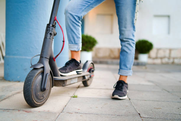 close up on woman legs feet standing on the electric kick scooter on the pavement wearing jeans and sneakers in summer day - electric push scooter stock photos and pictures