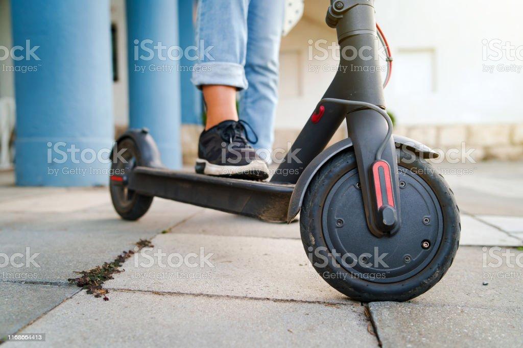 De cerca en los pies de las piernas de la mujer de pie en el patinete eléctrico en el pavimento usando jeans y zapatillas en el día de verano - Foto de stock de Actividad de fin de semana libre de derechos