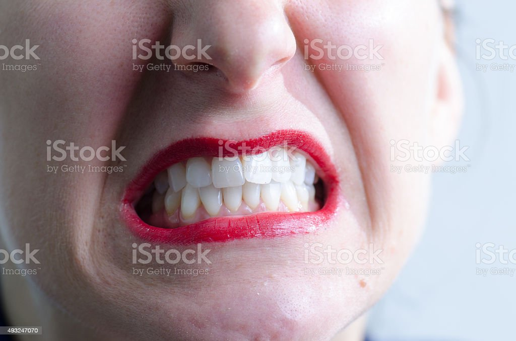 Close up on woman mouth grimacing and angry stock photo
