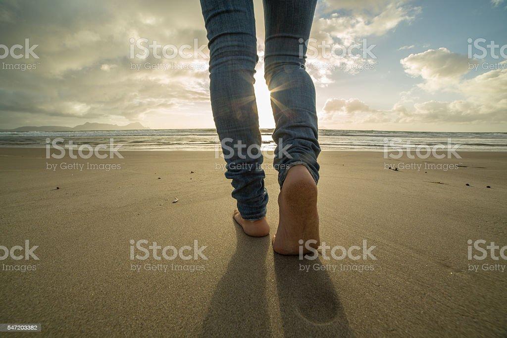 Close up on woman's feet walking on sandy beach, sunbeam stock photo