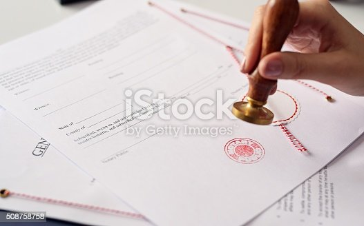 854317150istockphoto Close up on woman's notary public hand  stamping the document 508758758