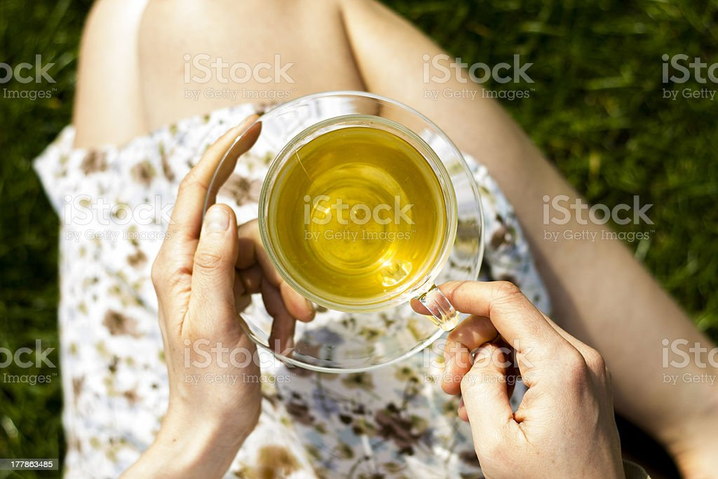 Close up on young woman's hands holding cup of tea stock photo