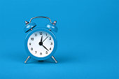 istock Close up one blue alarm clock over blue background 1125147553