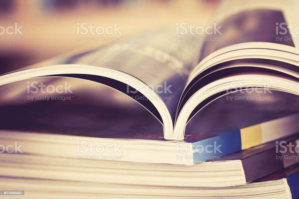 Close up opened magazine page with  blurry bookshelf background stock photo