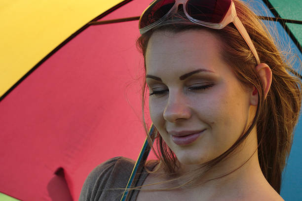 eyes closed rainbow umbrella demure blonde outdoor polish girl - whiteway polish outdoor girl stock photos and pictures