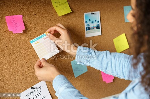 Close up over shoulder view of young african american woman pin weekly planning sticker on mood board at home office. Girl put post it sticky note memo on noticeboard to organize life and work concept