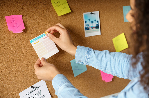 Close Up Over Shoulder View Of Young African American Woman Pin Weekly Planning Sticker On Mood Board At Home Office Girl Put Post It Sticky Note Memo On Noticeboard To Organize Life And Work Concept Stock Photo - Download Image Now