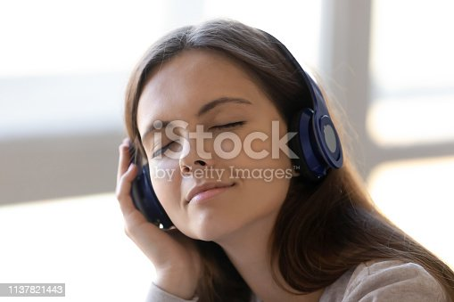 Close up peaceful woman in headphones enjoying favorite music, satisfied girl with closed eyes listening to pleasant song, relaxing with track for meditation, stress relief concept