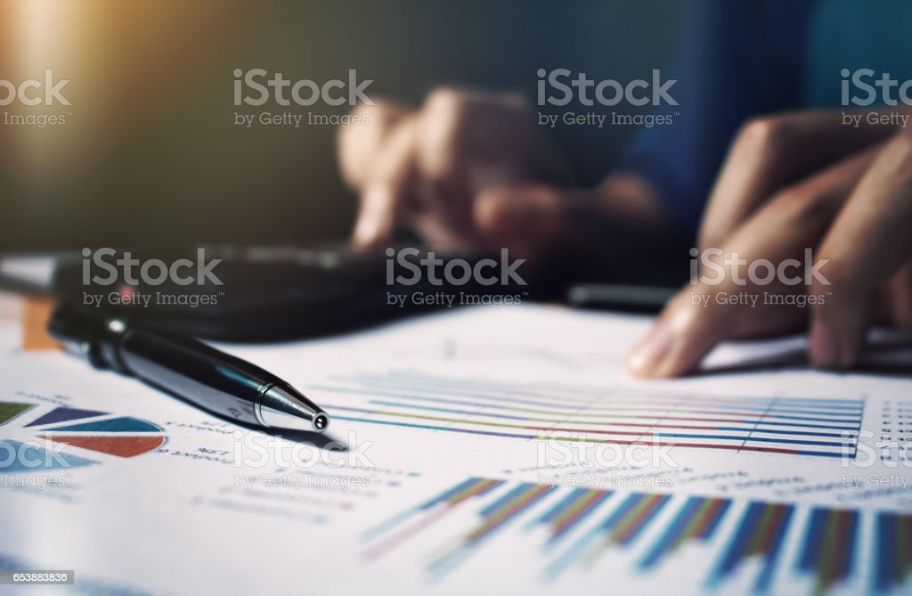 Close up pen on paperwork and woman hand calculate finance. stock photo