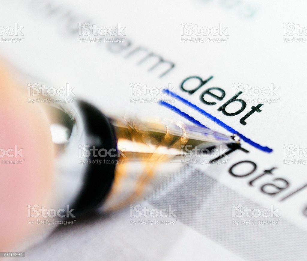 Close up pen underscores word 'debt' on financial document stock photo