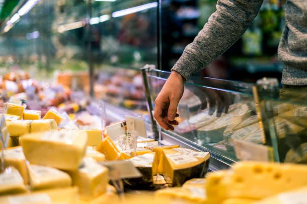 nahaufnahme der person die wahl käse in der lebensmittel-laden - teller kaufen stock-fotos und bilder