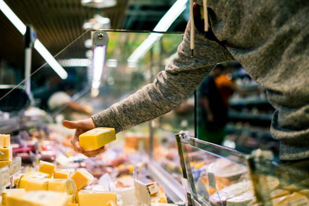 cerrar una mano persona compra queso en la tienda - tienda delicatessen fotografías e imágenes de stock