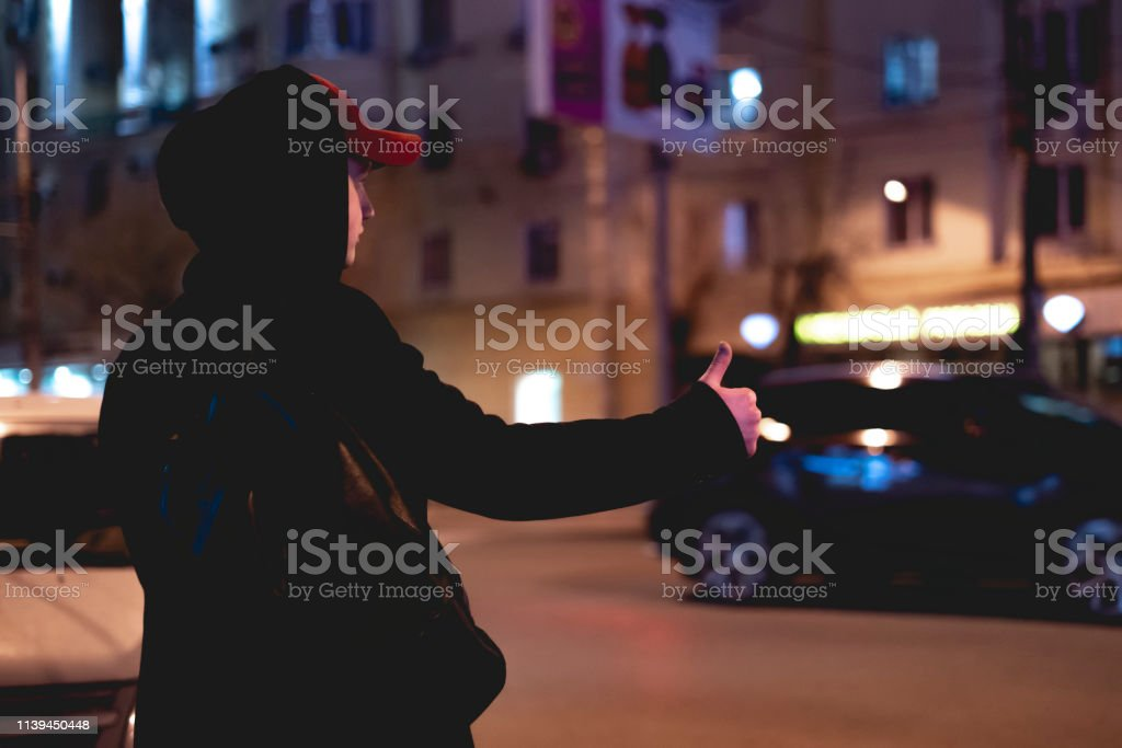 close up person hand hitch-hiking and waiting for a car stand on a...