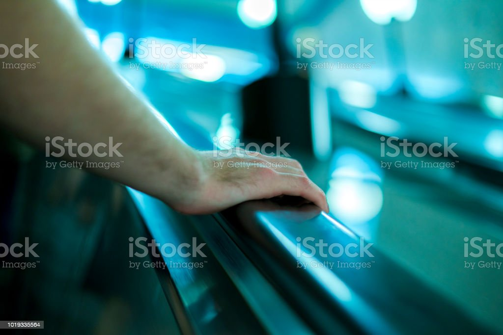 close up person\'s hand moving up on the escalator in subway