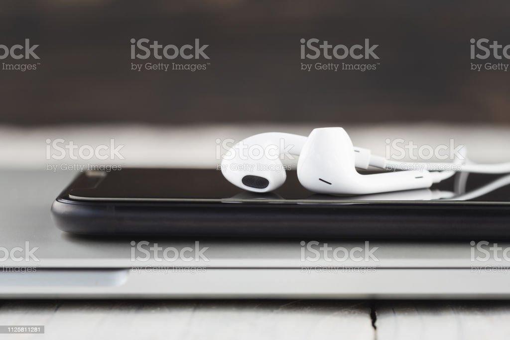 Telefon und Kopfhörer-Stack auf Laptop Computer Vorderansicht hautnah – Foto