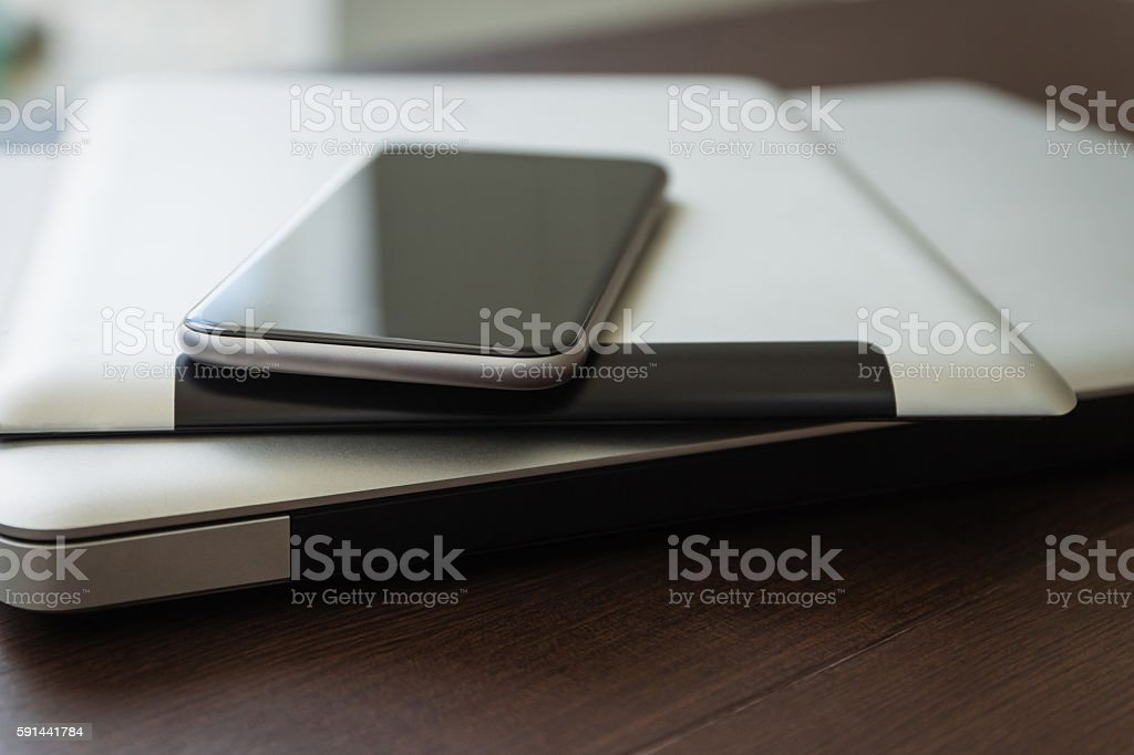 close up phone on tablet and laptop, new technology concept close up phone on tablet and laptop, new technology concept Business Stock Photo
