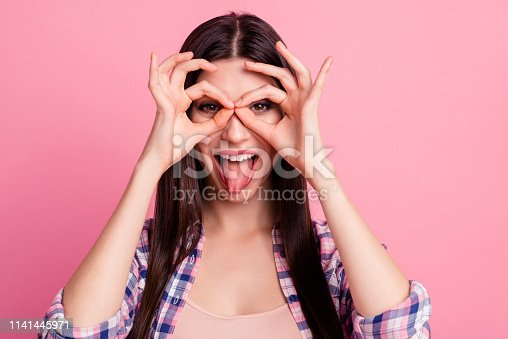 Close up photo amazing beautiful her she lady hold arm hand fingers okey symbol near brown eyes playful mood tongue out mouth wear casual checkered plaid shirt clothes outfit isolated pink background.