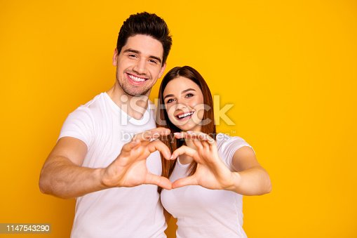 950598260 istock photo Close up photo amazing beautiful she her he him his guy lady hands arms fingers make heart figure form romance mood hugging sincere wear casual white t-shirts outfit isolated yellow background 1147543290