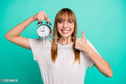 Close up photo amazing beautiful she her lady hold raise arm hand metal alarm clock hold thumb up recommending advising wear specs casual white t-shirt clothes isolated teal green background.