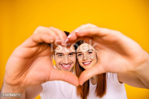 950598260 istock photo Close up photo amazing pretty she her he him his guy lady hands arms fingers make heart figure faces inside form just married romance mood wear casual white t-shirts outfit isolated yellow background 1147543711
