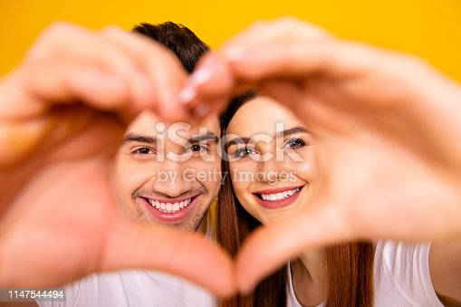 950598260 istock photo Close up photo amazing pretty she her he him his guy lady hands arms fingers make heart figure faces inside form married spouse romance wear casual white t-shirts outfit isolated yellow background 1147544494