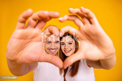 950598260 istock photo Close up photo amazing she her he him his guy lady hands arms fingers make heart figure faces inside form married spouse romance mood wear casual white t-shirts outfit isolated yellow background 1147544900